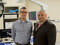 Dr. John Vozenilek poses with Dr. Greg Podolej in virtual Operating room